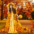 Woman autumn fashion portrait fall leaves model girl yellow park cape in season fantasy Royalty Free Stock Image