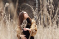 Woman in autumn in fur coat with owl on hand first snow. Beautiful brunette girl with long hair in nature, holding an owl Royalty Free Stock Photo