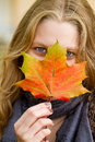 Woman with autumn leaf covered face colorful Stock Photography