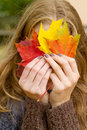 Woman with autumn leaf covered face colorful Royalty Free Stock Photography