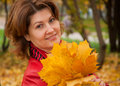 Woman in autumn park with a maple leaves Royalty Free Stock Photo