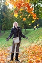 The woman in autumn park throws up red maple leaves in a sunny day beautiful Stock Photography