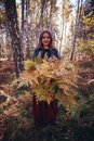 Woman autumn portrait. cute girl outdoors with a bouquet of yellow fern in the forest, autumn fall concept. Royalty Free Stock Photo