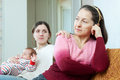 Woman with baby asks for forgiveness from mother her focus on mature Stock Image