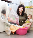 Woman with baby putting clothes into washing machine and looking at camera Stock Photo