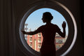 Woman on the background of round window dark silhouette a beautiful closed with blue sky Stock Photos