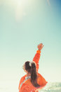 A woman in the background of the sea draws her hand to the sky. Back view Royalty Free Stock Photo