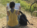 Woman with backpack and map sitting in dirtroad rear view of a young Royalty Free Stock Image