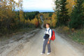 The woman with a backpack on the road goes way to mountain Stock Photo
