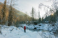 Woman with backpack walks along the mountain river in the snowdr Royalty Free Stock Photo