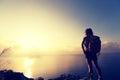 Woman backpacker enjoy the view at sunrise seaside mountain peak Royalty Free Stock Photo