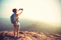Woman backpacker taking photo with cellphone on mountain peak Royalty Free Stock Photo