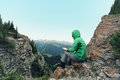 Woman backpacker use digital tablet taking photo on mountain peak cliff Royalty Free Stock Photo