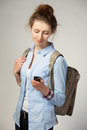 Woman with bag and mobile phone young holding a grey background Stock Photo