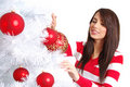 Woman with balls next to christmas tree Royalty Free Stock Image