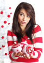 Woman with balls next to christmas tree Stock Photo