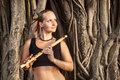Woman with bamboo flute indian bansuri near banyan tree in goa india Stock Photo