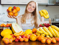 Woman with bananas and other fruits in home kitchen positive blonde long haired Royalty Free Stock Images