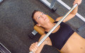 Woman with barbell on a bench press training beautiful doing exercises in fitness center Royalty Free Stock Photos