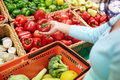 Woman with basket buying peppers at grocery store Royalty Free Stock Photo