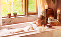 Woman bathing with pleasure lying down in the tub foam and looking in the window spending time in luxury spa resort Royalty Free Stock Images