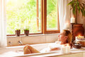 Woman bathing with pleasure lying down in the tub foam and looking in the window spending time in luxury spa resort Royalty Free Stock Image