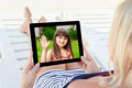 Woman in a bathing suit lying on a chaise lounge with a tablet a computer and communicates by video voice chat young child Royalty Free Stock Photography