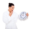 Woman bathrobe clock overslept in looking at the Stock Photos