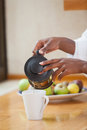 Woman in bathrobe pouring coffee Royalty Free Stock Photo