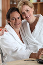 Woman in a bathrobe sitting on her partner s lap Royalty Free Stock Image