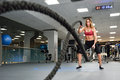 Woman with battle ropes exercise in the fitness gym.