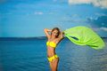 Woman at the beach holding sarong up in the air Royalty Free Stock Photo