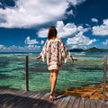 Woman on a beach jetty at seychelles la digue with sarong tropical Stock Photos