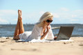 Woman at a beach with a laptop Stock Image