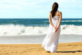 Woman on beach looking the sea young brunette in summer white dress standing and to caucasian girl relaxing and enjoying peace Royalty Free Stock Image