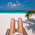 Woman at beach lying on chaise lounge beautiful Stock Photography