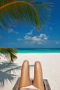 Woman at beach lying on chaise lounge beautiful Royalty Free Stock Image
