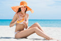 Woman at beach with moisturizer happy young in bikini applying Royalty Free Stock Photo