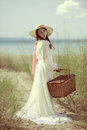 Woman at the beach with picnic basket portrait of a Royalty Free Stock Images