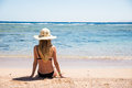 Woman on beach sitting in sand looking at ocean enjoying sun and summer travel holidays vacation getaway. Girl in bikini relaxing Royalty Free Stock Photo