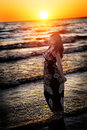 Woman on the beach. Sunset, sea and waves. Red sunlight Royalty Free Stock Photo