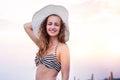 Woman on beach wearing bikini and hat, smiling, holding head Royalty Free Stock Photo