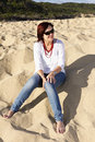 Woman on the beach wearing sunglasses a middle aged sitting with she is relaxing vacation Royalty Free Stock Images
