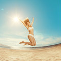 Woman on the beach young girl on the sand by sea stylish beaut beautiful beautiful smiling in a jump against sun Royalty Free Stock Image