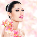 Woman with beautiful face and fresh flowers young skin care concept Stock Images