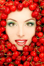 Woman beautiful face with red ripe big fresh cherry