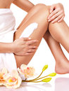 Woman with a beautiful with flowers body using a cream on her leg on white background Royalty Free Stock Photo