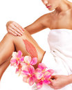 The woman with a beautiful with flowers body using a scrub flower on her leg on white background Royalty Free Stock Photography
