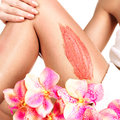 The woman with a beautiful with flowers body using a scrub flower on her leg on white background Stock Images