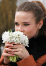 Woman beautiful girl smell and enjoy fragrance of snowdrop flowers Royalty Free Stock Images